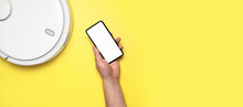 White Modern Robot Vacuum Cleaner, Smartphone With White Blank Screen In Male Hands On Yellow Background Flat Lay. New Technologies. Controlling The Vacuum Cleaner From Your Phone Automatic Assistant