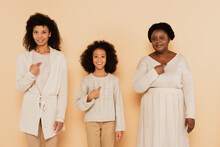 African American Daughter, Granddaughter And Grandmother Pointing With Fingers To Themselves On Beige Background