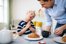 Down Syndrome Boy With Father At The Table, Having Breakfast.