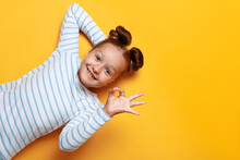 Top View Of A Cute Adorable Little Girl With Bundles Of Hair On A Yellow Background. The Child Shows The Sign Ok. Close Up Copy Space.