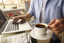 Man With Cup Of Coffee Working On Laptop At Outdoor Cafe In Morning, Closeup