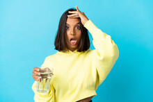 Young Asiatic Woman With A Glass Of Water Isolated On Blue Background Doing Surprise Gesture While Looking To The Side