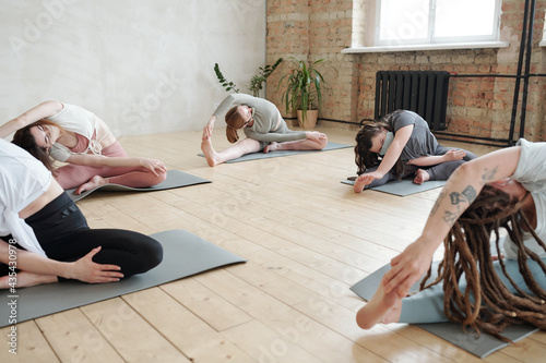 Foto Females in masks doing side-bends on mats while practicing yoga in gym