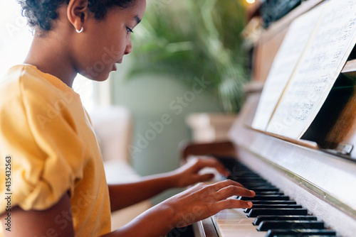 Obraz na plátně Musical education. Happy black girl playing the piano