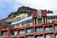 Steep Hillside With Holiday Hotel Complex Against Blue Sky