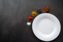 A White Empty Plate With Space For Text, Around Which Various Spices Are Scattered In Piles. On A Black Background. Copy Space