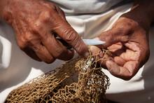 Fisherman's Hand Repairing A Fishing Net.