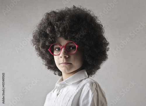 portrait of young boy with a curly wig