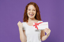 Young Happy Redhead Caucasian Woman 20s In White Basic Blank Print Design T-shirt Holding Gift Voucher Flyer Mock Up Do Winner Gesture Clench Fist Isolated On Dark Violet Background Studio Portrait