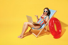 Full Body Length Happy Young Woman Wear Red Blue One-piece Swimsuit Sit On Chair Work Hold Laptop Pc Isolated Over Vivid Yellow Color Wall Background Studio Summer Hotel Pool Sea Rest Sun Tan Concept
