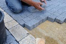 A Worker Made A Sidewalk From Bricks.