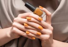 Female Hands With Orange Nail Design. Glitter Orange Nail Polish Manicure. Woman Hold Orange Nail Polish Bottle.