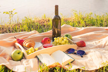 Picnic By The River. On A Light-colored Bedspread, A Wooden Tray With Fruit, Cakes And A Bottle Of Wine. The Light Of The Setting Sun, A Pleasant Calm Atmosphere, Bright Colors.