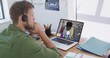Caucasian man wearing phone headset having a video call with female colleague on laptop at office