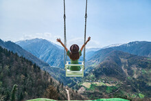 Free Happy Joyful Woman Traveler With Open Arms Swinging On Chain Swing In The Mountains, Enjoying Beautiful View And Good Life Moment