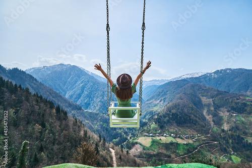 Fotografía Free happy joyful woman traveler with open arms swinging on chain swing in the m