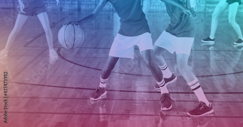 Composition of group of fit basketball players playing match over light blur