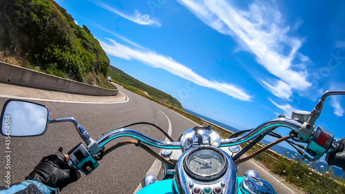 Fotografiet Classic motorcycle ride on a winding road in springtime