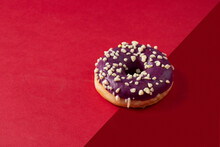 Blueberry Glaze Donut With Nuts  Topping On Two Colour Background