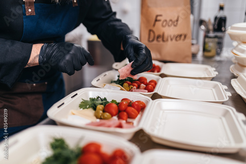Food in disposable dishes ready for delivery. The chef prepares food in the restaurant and packs it in disposable lunch boxes.