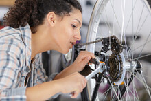 Female Mechanic Tightening Pedal On Bicycle