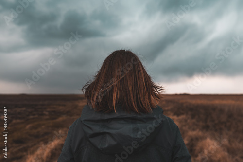 Fotografie, Obraz Woman standing in meadow, looking at the horizon and dark dramatic stormy clouds