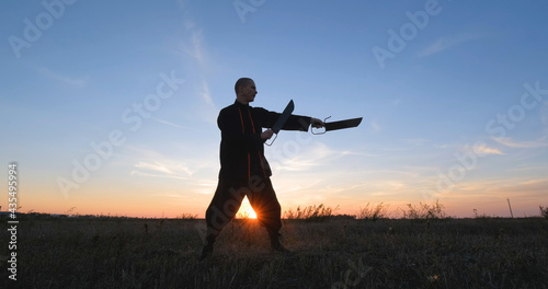 Obraz na plátně Silhouette of young male kung fu fighter practising alone in the fields during s