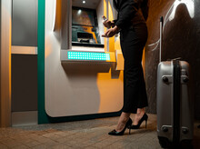 Businesswoman With Luggage Spraying Alcohol Hand Sanitizer On Hands After Using ATM, No Face