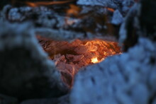Close Up Peering Into The Hot Core Of A Fire Pit Through Burnt Logs.
