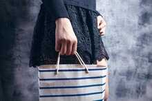 Young Woman Stands With A Gift Bag