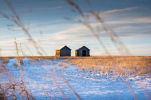 Two Vintage Grain Sheds On A Harvested Field During The Spring At Sunrise In Rocky View County Alberta Canada.