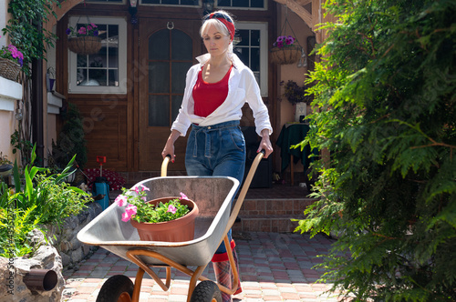 Fotomural Beautiful blond middle aged woman in white shirt and blue jeans pushing a handca