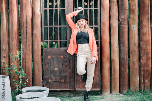 Fotografie, Obraz Photography of a model posing, wearing an elegant skirt, boots, and glasses, with fashion style