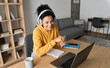 Young happy smiling African American adult student wearing headphones having virtual education class meeting online call e learning webinar on laptop at home office writing notes.