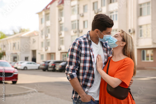 Valokuva Couple in medical masks trying to kiss outdoors