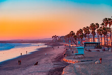 A Oceanside Sunset At The Beach Draws People To It To Walk And Relax And The Ocean Shoreline.