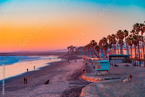 Fotografia A Oceanside sunset at the beach draws people to it to walk and relax and the ocean shoreline