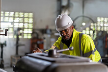 African American Male Engineer Worker Maintenance Heavy Machine In The Factory. Black Male Worker Working With Heavy Machine With Safety Uniform, Goggles And Helmet