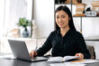 Portrait of a pretty asian young woman. Successful confident japanese female office worker, wearing formal shirt, sitting at her workplace with laptop, looking at the camera, smiling friendly