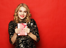 Portrait Of A Happy Smiling Woman In Dress Holding Present Box Isolated Over Red Background