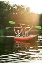 Couple Of Excited Friends Having Fun While Kayaking In A River Surrounded By The Beautiful Nature On A Summer Day