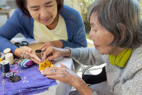 Elderly woman and daughter in the needle crafts occupational therapy for Alzheim Fotobehang