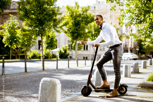 Obraz na plátně Young African American using electric scooter on a street