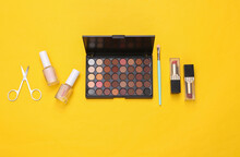 Beauty Products On Yellow Background. Make Up Eye Shadow Palette, Makeup Brushes, Scissors And Nail Polish. Top View. Flat Lay