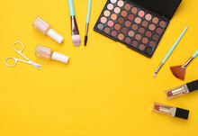 Beauty Products On Yellow Background. Make Up Eye Shadow Palette, Makeup Brushes, Scissors And Nail Polish. Top View. Flat Lay. Copy Space