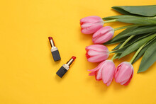 Lipsticks And Pink Tulips On Yellow Background. Romantic, Beauty Concept