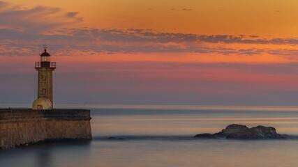 Latarnia morska nad Oceanem Atlantyckim w zachodzącym słońcu
