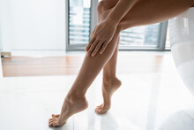 Hand, Slim Ankle And Foot Of Woman Touching Smooth Hairless Leg Skin, Applying Lotion Or Oil For Moisturizing Body Skin After Depilation, Hair Removal Procedure. Beauty Care Concept. Close Up