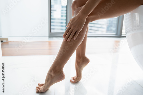 Fotografía Hand, slim ankle and foot of woman touching smooth hairless leg skin, applying lotion or oil for moisturizing body skin after depilation, hair removal procedure