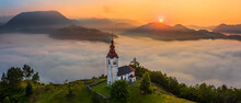 Sebrelje, Slovenia - Aerial Panoramic Drone View Of The Beautiful Hilltop Church Of St.Ivan (Sv. Ivan Cerkev) At Sunrise With Huge Morning Fog Bellow The Valley And Julian Alps At Background